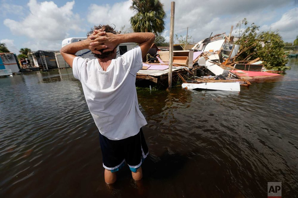 In this Sept. 11, 2017 photo, Larry Dimas walks around his destroyed trailer in Immokalee, Fla. Irma badly damaged Dimas' mobile home and destroyed another he used for rental income, making his tough life even harder. (AP Photo/Gerald Herbert)