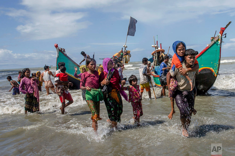Rohingya Muslims walk to the shore after arriving on a boat from Myanmar to Bangladesh in Shah Porir Dwip, Bangladesh, Thursday, Sept. 14, 2017. Nearly three weeks into a mass exodus of Rohingya fleeing violence in Myanmar, thousands were still flooding across the border Thursday in search of help and safety in teeming refugee settlements in Bangladesh. (AP Photo/Dar Yasin)