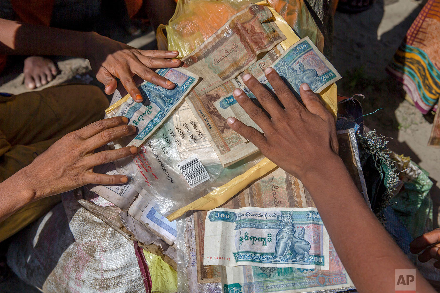 Rohingya Muslim boys, who crossed over from Myanmar into Bangladesh, dry their Myanmarese currency after arriving by boat at Shah Porir Dwip, Bangladesh, Thursday, Sept. 14, 2017. (AP Photo/Dar Yasin)
