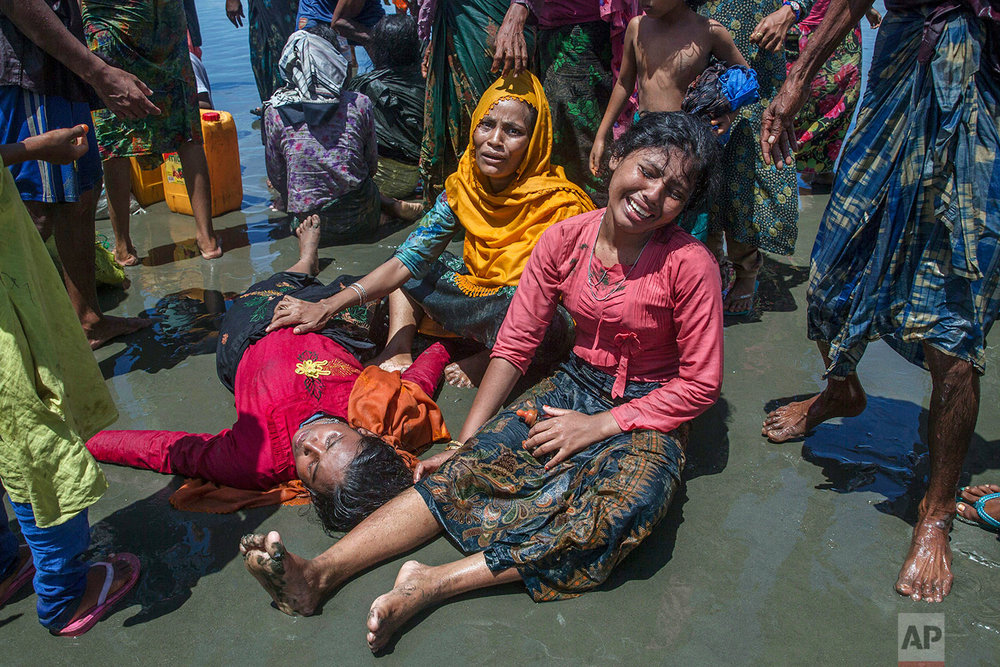 Rohingya Muslim women, who crossed over from Myanmar into Bangladesh, wail as a relative lies unconscious after the boat they were traveling in capsized minutes before reaching shore at Shah Porir Dwip, Bangladesh, Thursday, Sept. 14, 2017. The woman survived. (AP Photo/Dar Yasin)