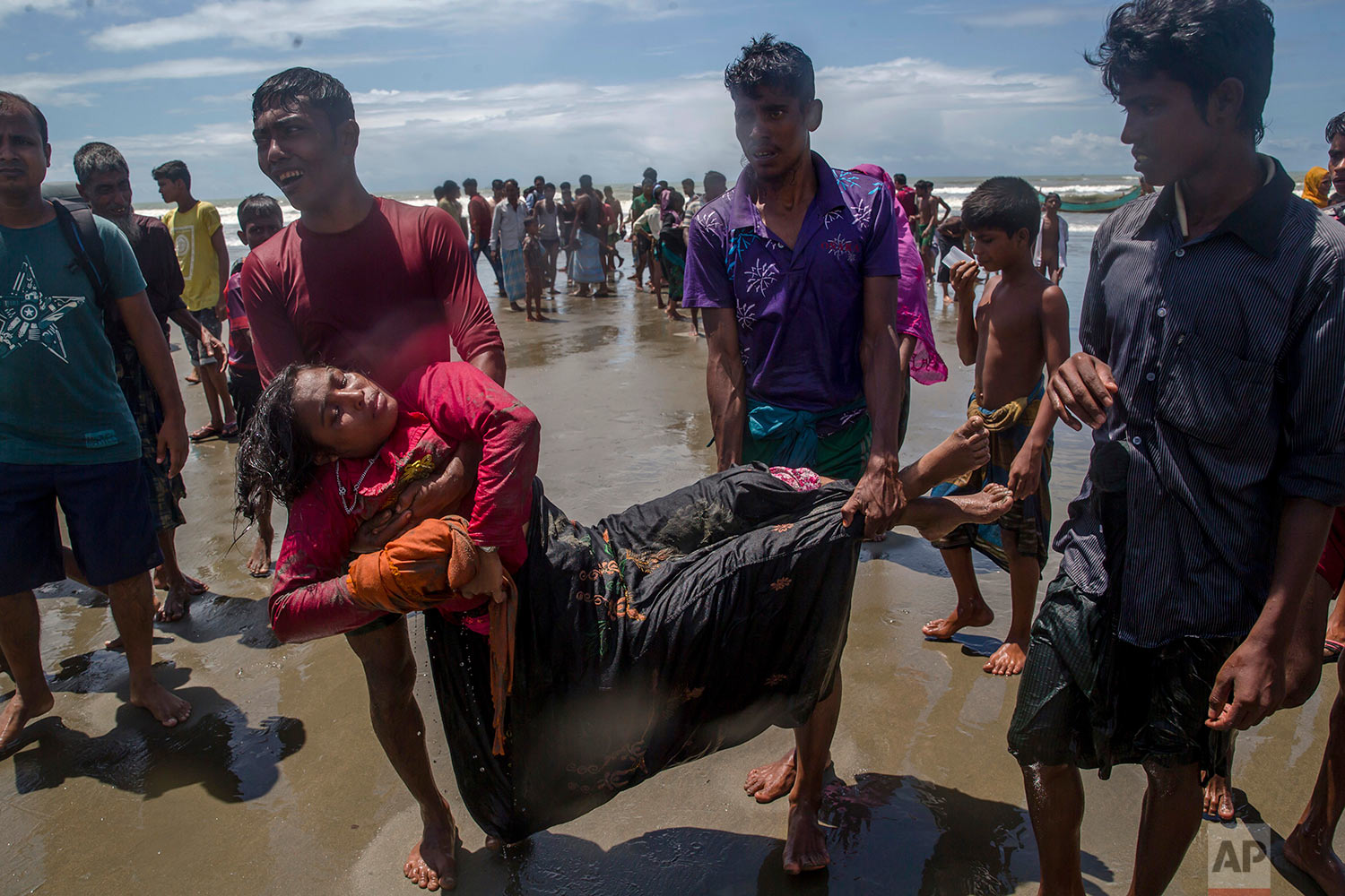 Relatives carry a Rohingya Muslim woman, who fell unconscious when the boat she was traveling in capsized minutes before reaching shore, towards a medical center for treatment at Shah Porir Dwip, Bangladesh, Thursday, Sept. 14, 2017. The woman survived. (AP Photo/Dar Yasin)