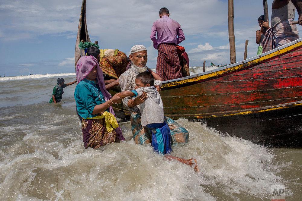 An elderly Rohingya Muslim man helps a boy get off a boat after they arrived from Myanmar to Bangladesh in Shah Porir Dwip, Bangladesh, Thursday, Sept. 14, 2017. (AP Photo/Dar Yasin)