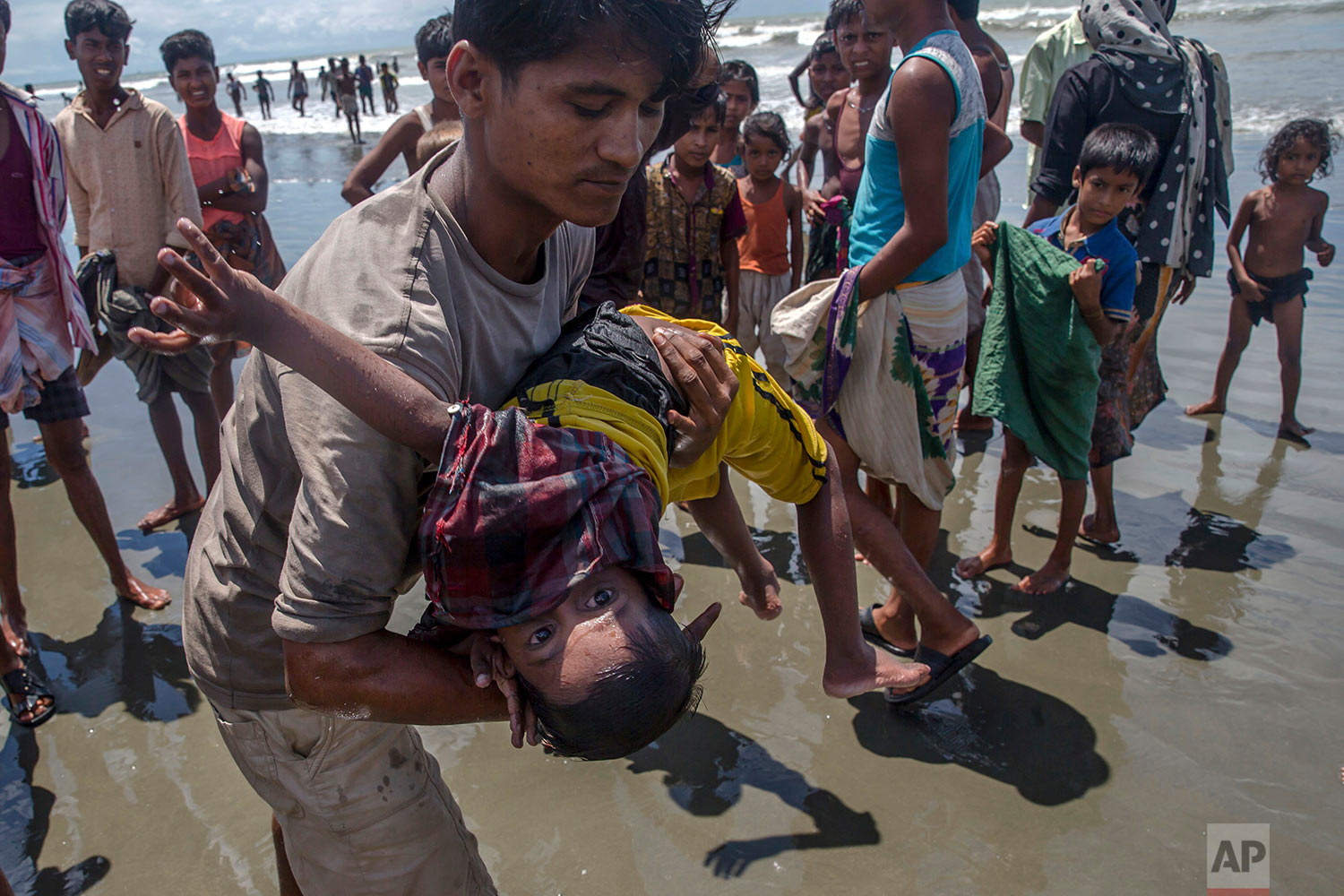 A man shakes a Rohingya Muslim boy while trying to revive him after the boat he was traveling in capsized just before reaching shore at Shah Porir Dwip, Bangladesh, Thursday, Sept. 14, 2017. (AP Photo/Dar Yasin)