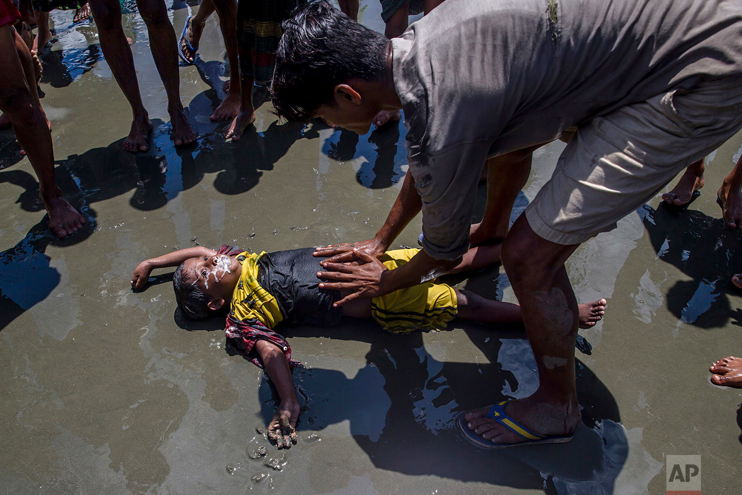 A Rohingya Muslim boy froths from the mouth as a man successfully tries to revive him after the boat he was traveling in capsized just before reaching shore at Shah Porir Dwip, Bangladesh, Thursday, Sept. 14, 2017.  (AP Photo/Dar Yasin)