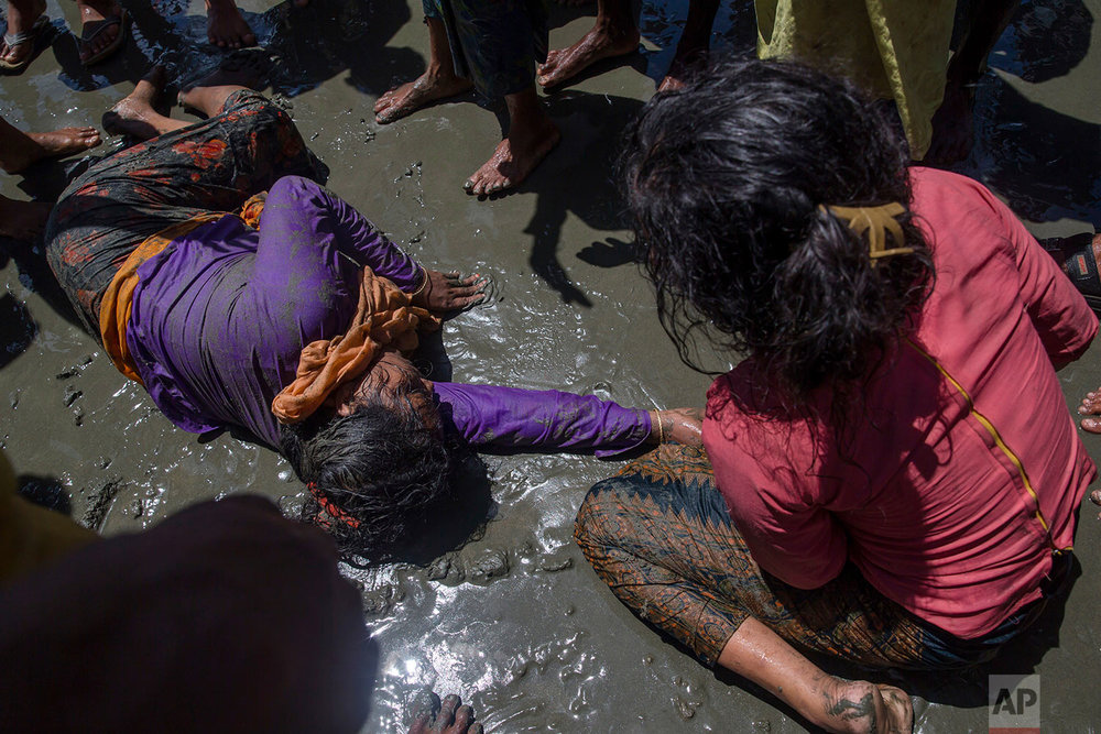 A Rohingya Muslim woman, who crossed over from Myanmar into Bangladesh, lies unconscious on the shore of Bay of Bangal after the boat she was traveling in capsized at Shah Porir Dwip, Bangladesh, Thursday, Sept. 14, 2017. (AP Photo/Dar Yasin)