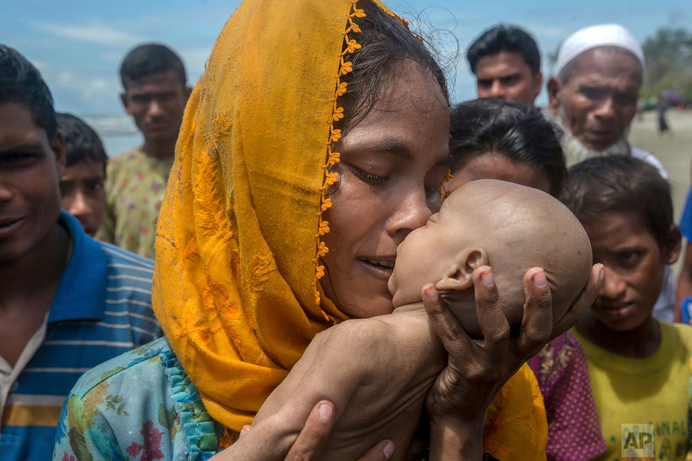 A Rohingya Muslim woman Hanida Begum, who crossed over from Myanmar into Bangladesh, kisses her infant son Abdul Masood who died when the boat they were traveling in capsized just before reaching the shore of the Bay of Bengal, in Shah Porir Dwip, Bangladesh, Thursday, Sept. 14, 2017. (AP Photo/Dar Yasin)