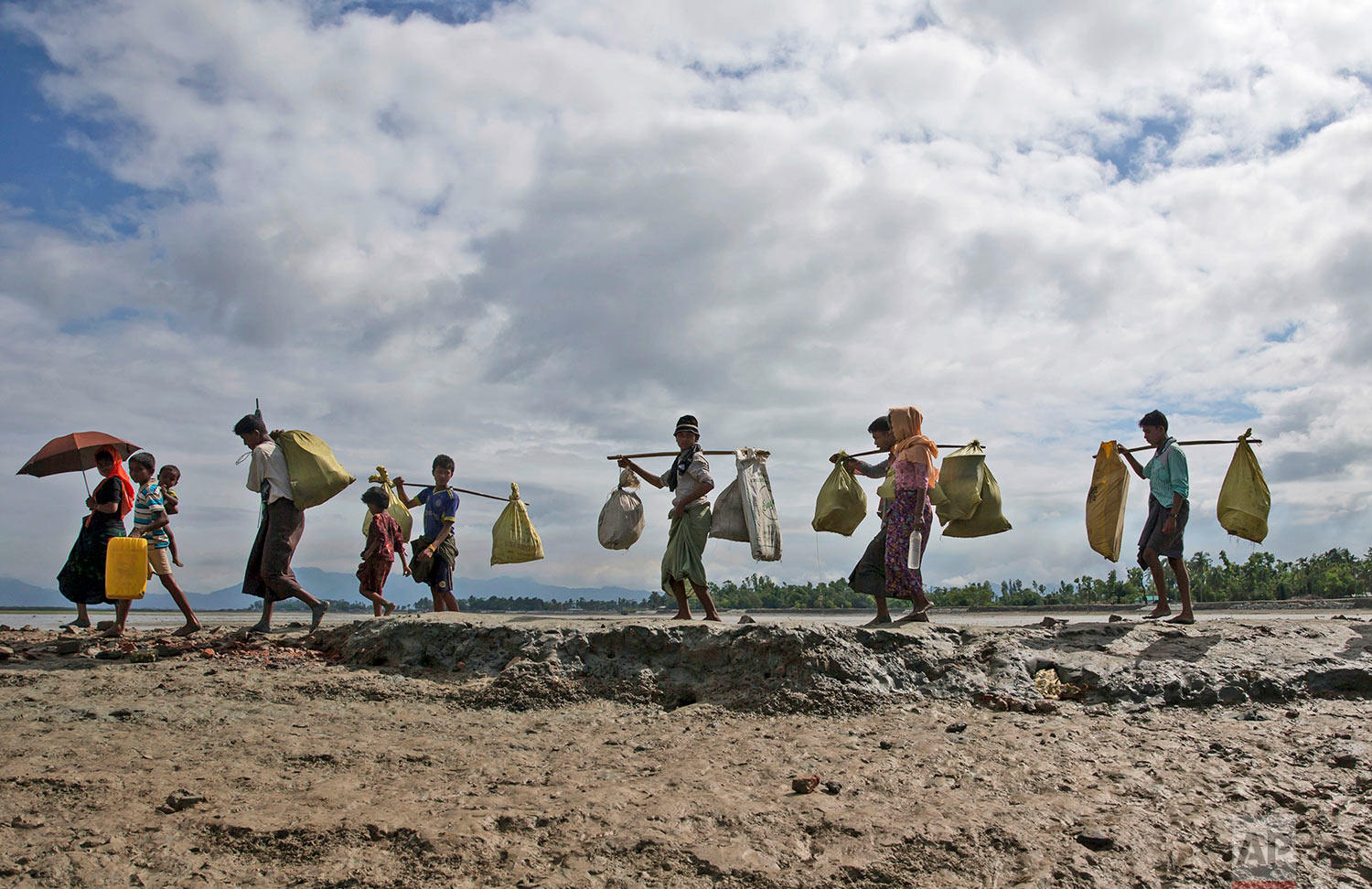 Rohingya Muslims, who crossed over from Myanmar into Bangladesh, walk towards a refugee camp in Shah Porir Dwip, Bangladesh, Thursday, Sept. 14, 2017. Nearly three weeks into a mass exodus of Rohingya fleeing violence in Myanmar, thousands were still flooding across the border Thursday in search of help and safety in teeming refugee settlements in Bangladesh. (AP Photo/Dar Yasin)