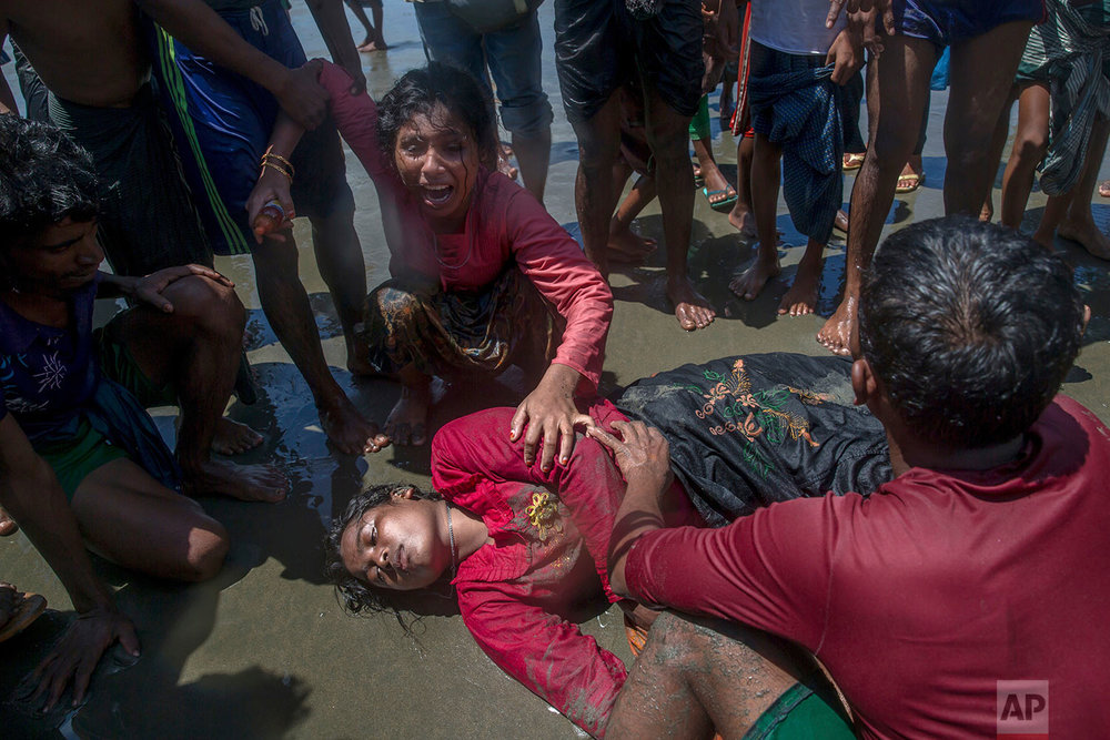 A Rohingya Muslim woman, who crossed over from Myanmar into Bangladesh, wails siting beside her relative who fell unconscious after the boat they were traveling in capsized at Shah Porir Dwip, Bangladesh, Thursday, Sept. 14, 2017. Nearly three weeks into a mass exodus of Rohingya fleeing violence in Myanmar, thousands were still flooding across the border Thursday in search of help and safety in teeming refugee settlements in Bangladesh. The woman survived. (AP Photo/Dar Yasin)