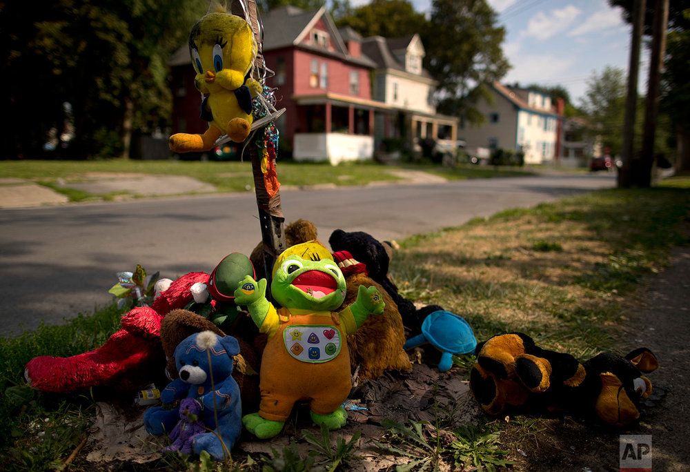 A make-shift memorial of stuffed animals decorates a South Side street corner, Monday, Aug. 21, 2017, in Syracuse, N.Y. The memorial was created for 15-year-old Akil Williams who was shot earlier this summer. (AP Photo/Julie Jacobson)