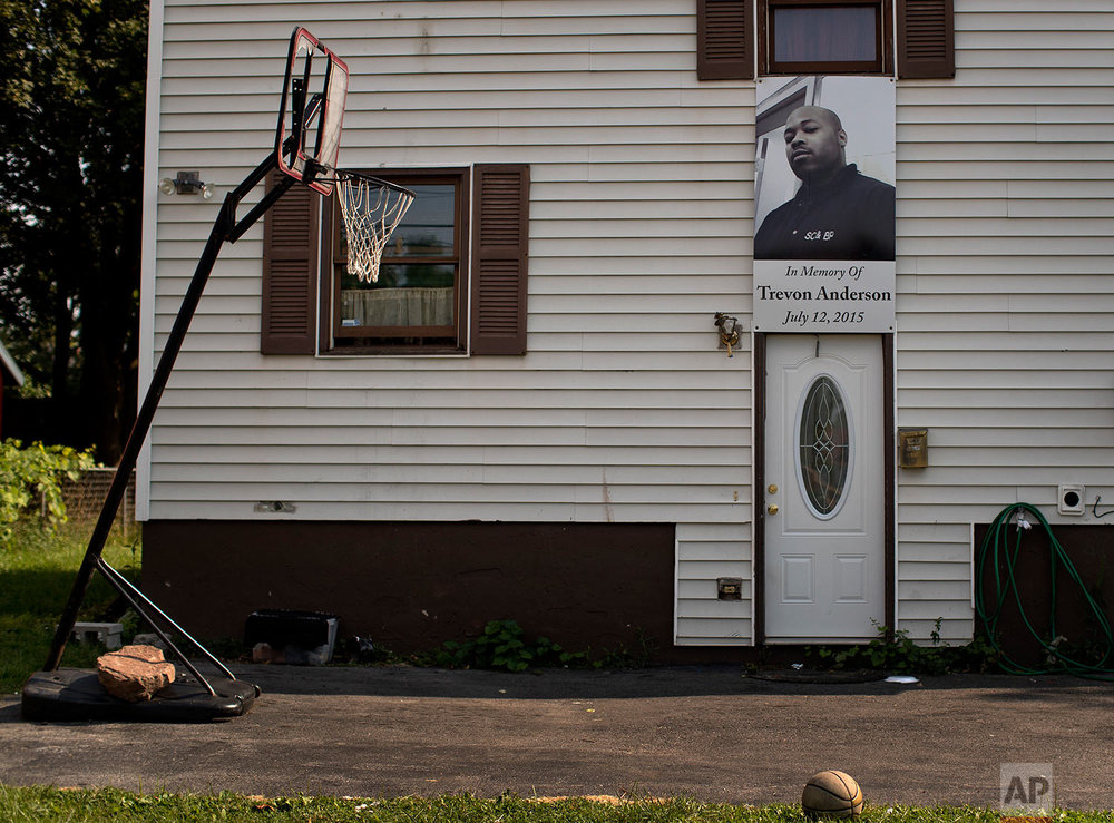 A photo of a victim of gun violence hangs over the entrance to a home, Monday, Aug. 21, 2017, in the South Side neighborhood of Syracuse, N.Y. (AP Photo/Julie Jacobson)