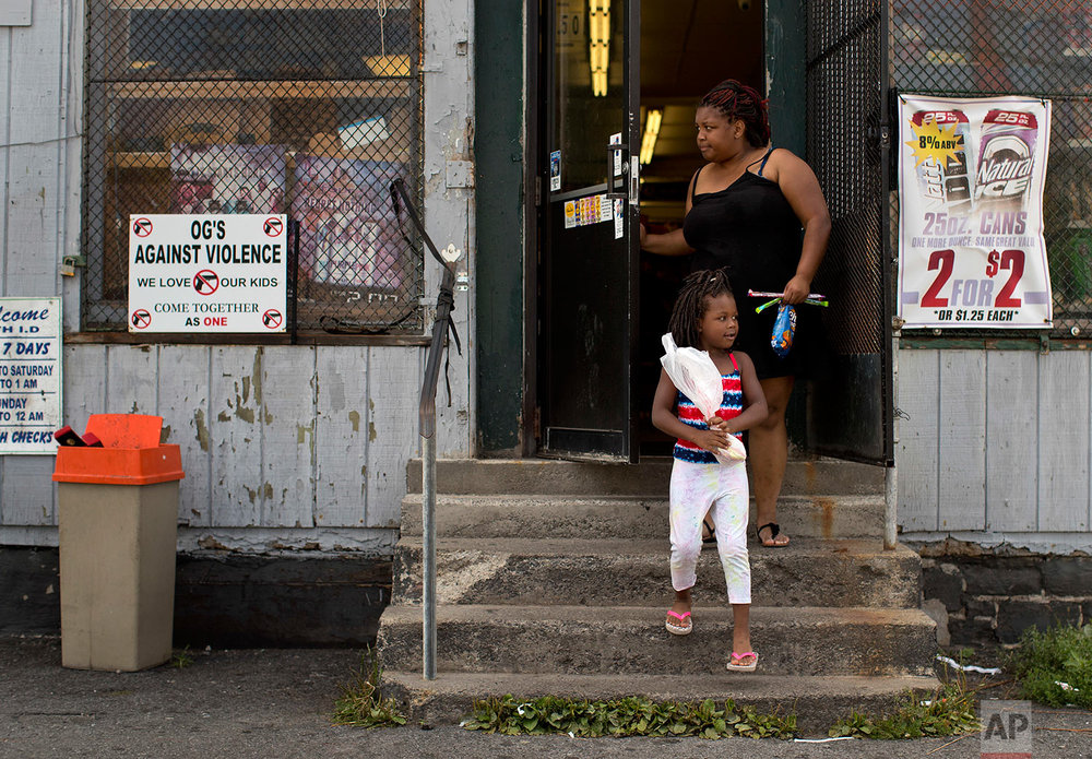 An anti violence sign, created by former gangsters hangs on a window of a corner convenience store where woman and her daughter finished shopping, Monday, Aug. 21, 2017, in the South Side neighborhood of Syracuse, N.Y. (AP Photo/Julie Jacobson)
