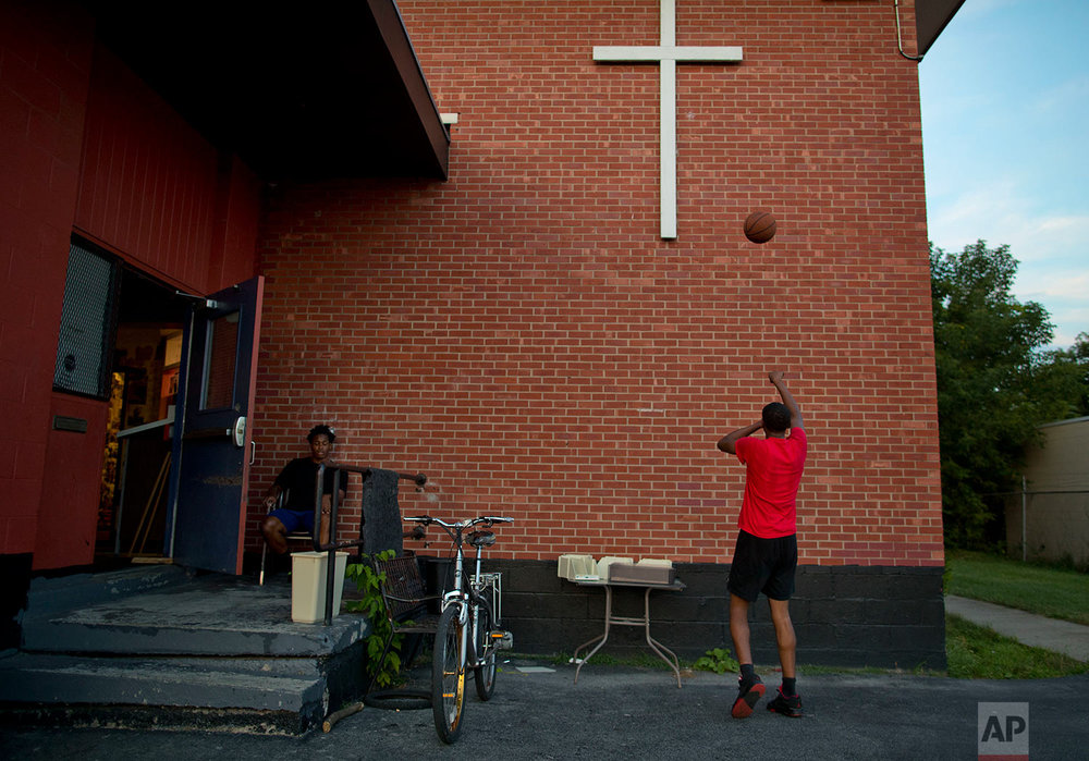 """Quishawn Richardson, right, shoots a basketball against the wall at the Faith and Hope Community Center, Monday, Aug. 21, 2017, in the South Side neighborhood of Syracuse, N.Y. The center """"doesn't remind you of all the violence that's going on outside,"""" said Quishawn, a lanky 15-year-old who dreams of playing basketball up the hill at the university. """"It shows you that Syracuse has got some places you can go to without getting hurt."""" (AP Photo/Julie Jacobson)"""
