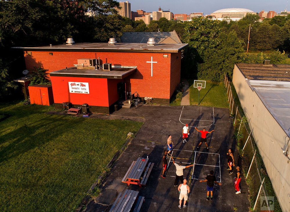 """A group of teenagers and young men exercise outside the Faith and Hope Community Center in the South Side neighborhood just down the hill from Syracuse University's Carrier Dome, Monday, Aug. 21, 2017, in Syracuse, N.Y. Coach and mentor Arthur """"Bobby"""" Harrison, who was serving in Attica state prison in 1971 during the infamously deadly uprising, believes in providing a firm hand for the teens who train here. (AP Photo/Julie Jacobson)"""