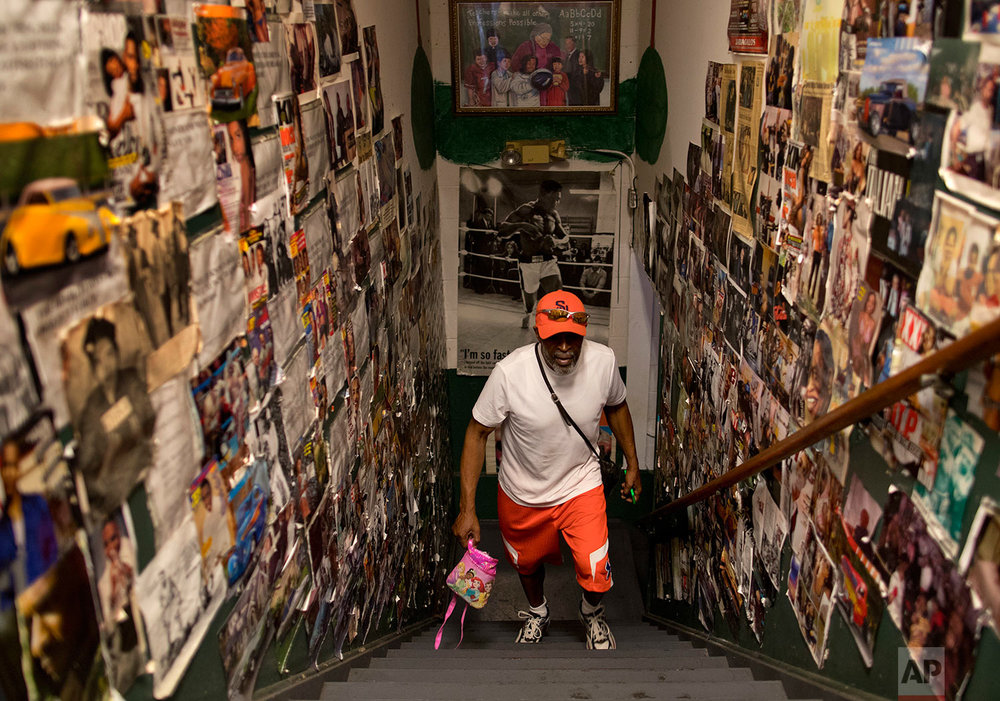 """Arthur """"Bobby"""" Harrison walks up the stairs from the basement of the Faith and Hope Community Center, Monday, Aug. 21, 2017, in Syracuse, N.Y. Newspaper and magazine clippings about local residents and sports and entertainment celebrities cover the walls where Harrison coaches and mentors teenagers and young men in hopes of keeping them out of trouble. (AP Photo/Julie Jacobson)"""