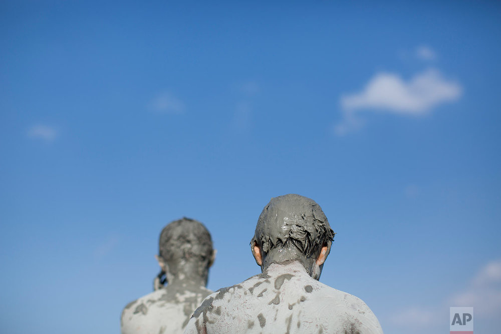 Two Israeli youth covered with mud during the annual Sea of Galilee swim, the oldest and largest popular swimming event, near Tiberias, northern Israel, Saturday, Sept. 16, 2017.  (AP Photo/Oded Balilty)
