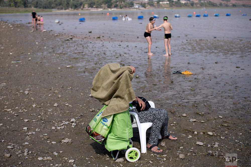 A person observes as swimmers participate in the annual Sea of Galilee swim, the oldest and largest popular swimming event, near Tiberias, northern Israel, Saturday, Sept. 16, 2017. (AP Photo/Oded Balilty)