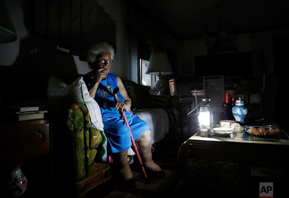 "Mary Della Ratta, 94, sits by a battery-powered lantern in her home three days after Hurricane Irma knocked out electricity in Naples, Fla., Wednesday, Sept. 13, 2017. ""I don't know what to do. How am I going to last here?"" said Della Ratta. In the immediate aftermath of Irma's fury, some 6.5 million homes and businesses - two-thirds of all accounts in the state - lost power amid the steamy late-summer heat. (AP Photo/David Goldman)"