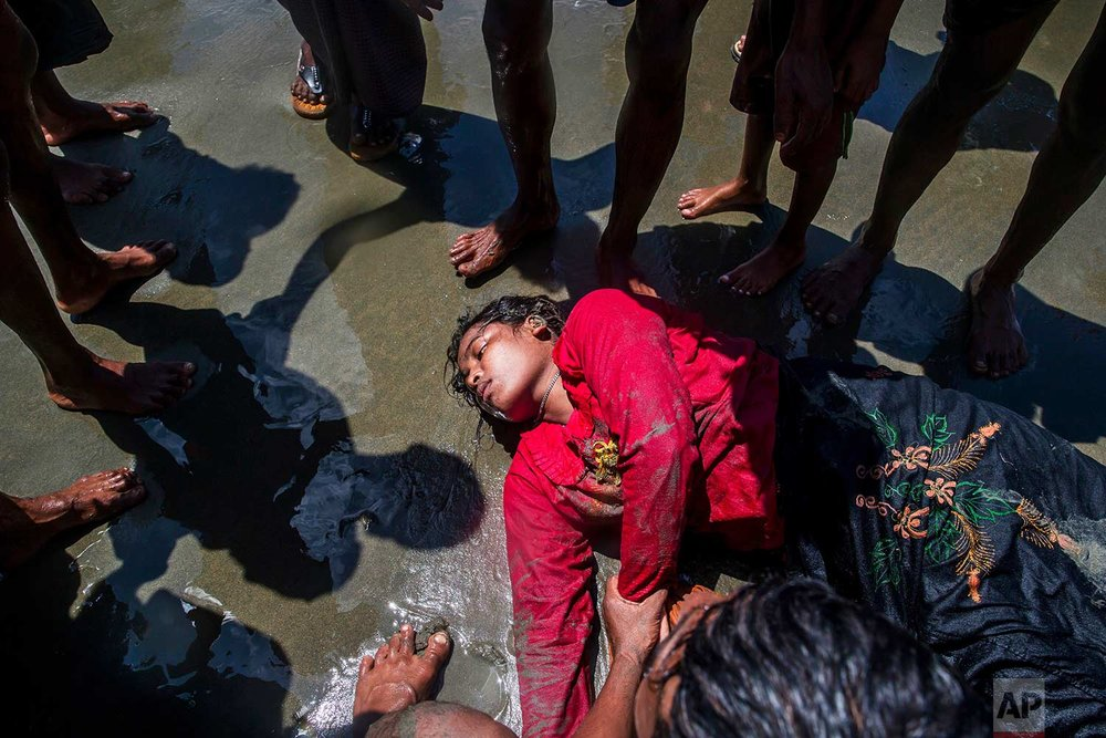 A Rohingya Muslim woman, who crossed over from Myanmar into Bangladesh, lies unconscious on the shore of the Bay of Bangal after the boat she was traveling in capsized at Shah Porir Dwip, Bangladesh, Thursday, Sept. 14, 2017. Nearly three weeks into a mass exodus of Rohingya fleeing violence in Myanmar, thousands were still flooding across the border Thursday in search of help and safety in teeming refugee settlements in Bangladesh. (AP Photo/Dar Yasin)
