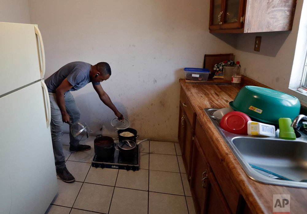 In this June 6, 2017 photo, Abelson Etienne removes the top to a pot of rice on a stove in his apartment in Tijuana, Mexico. (AP Photo/Gregory Bull)