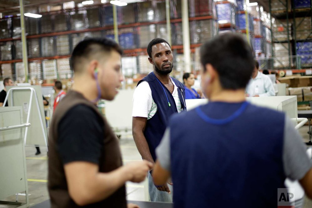 In this June 6, 2017 photo, Rodin St. Surin, of Haiti, looks on as coworkers talk on the floor of a factory in Tijuana, Mexico. (AP Photo/Gregory Bull)