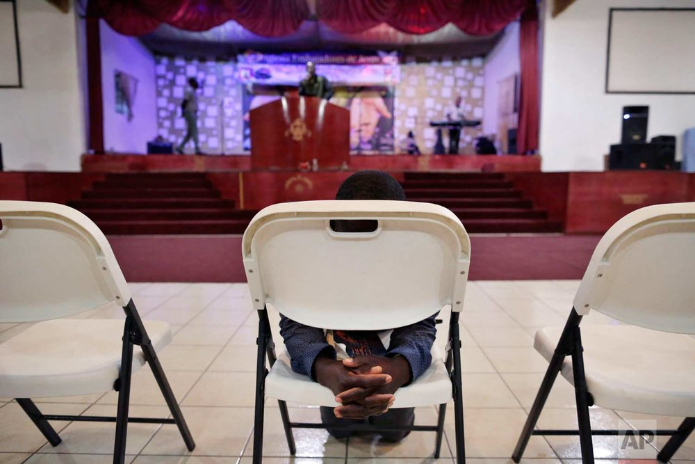 In this May 24, 2017 photo, Jeccene Thimote, of Haiti, kneels in front of a folding chair in prayer during a service in Creole at The Ambassadors of Jesus Church in Tijuana, Mexico. (AP Photo/Gregory Bull)