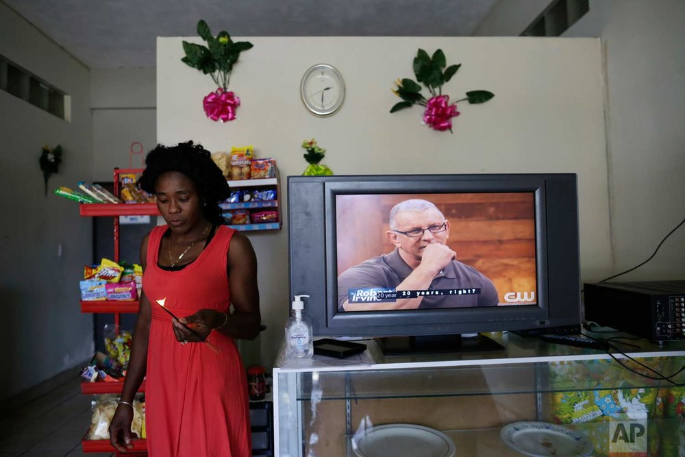In this May 24, 2017 photo, Lucy Charles, of Haiti, walks past a television in her restaurant specializing in Haitian cuisine in Tijuana, Mexico. (AP Photo/Gregory Bull)