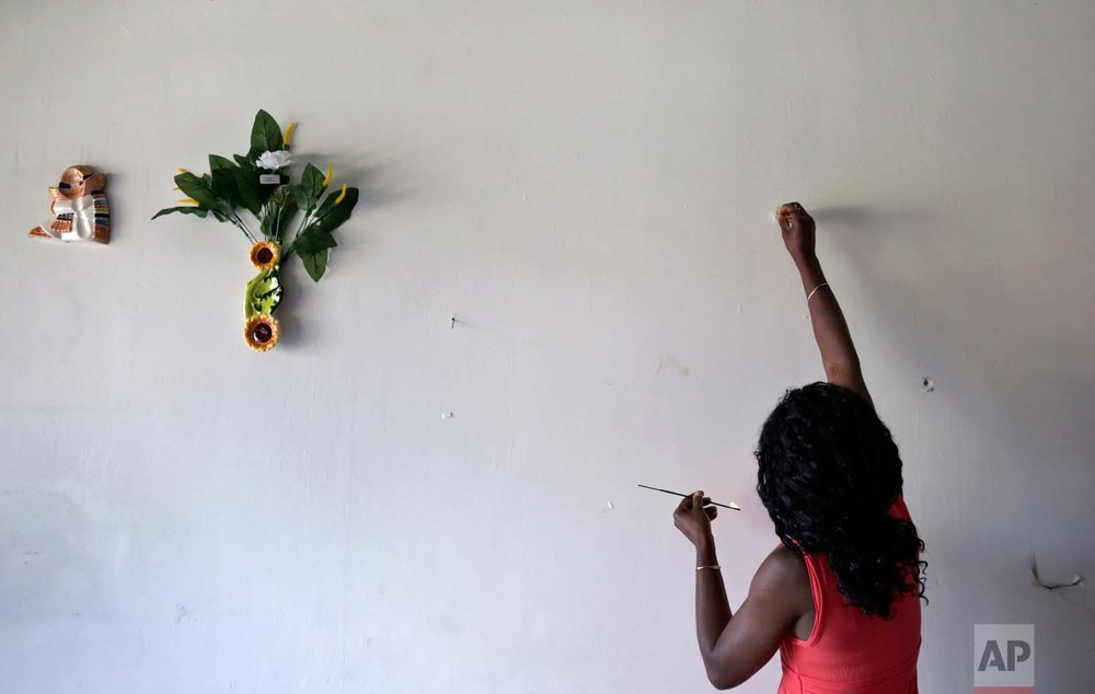 In this May 24, 2017 photo, Lucy Charles, of Haiti, lights incense along a wall in her restaurant specializing in Haitian cuisine in Tijuana, Mexico. (AP Photo/Gregory Bull)