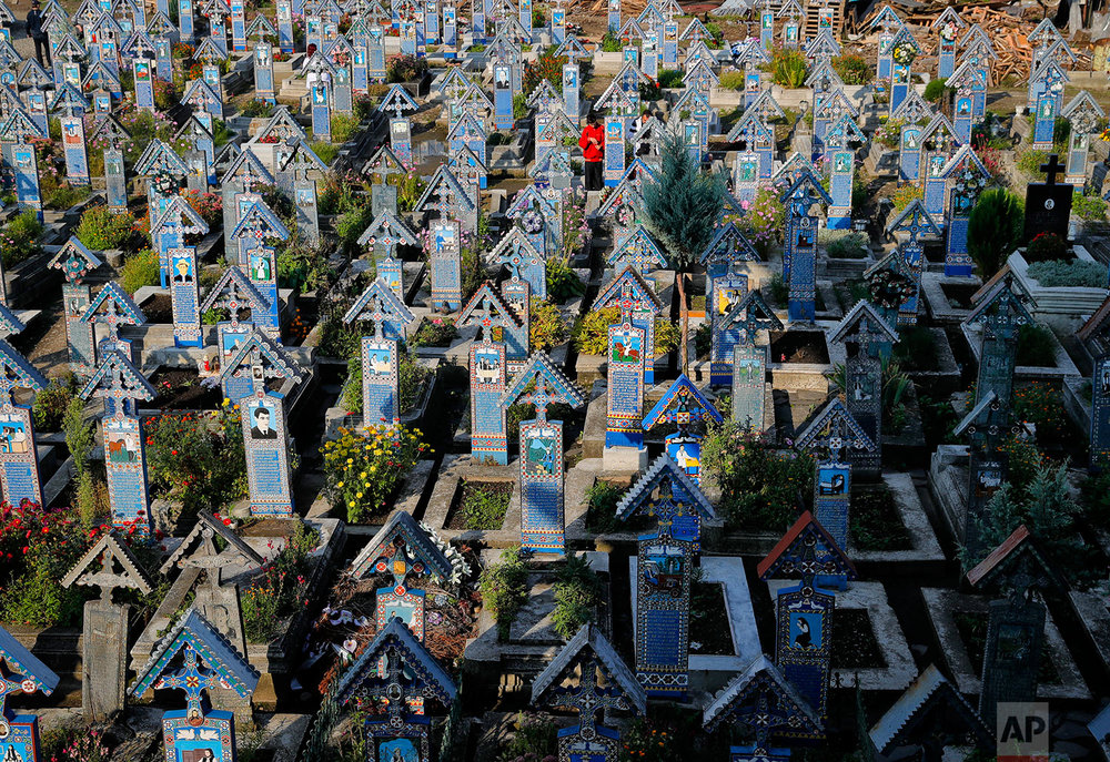 A man stands between the painted crosses in the Merry Cemetery, in Sapanta, northwestern Romania, Sunday, Sept. 10, 2017.  (AP Photo/Vadim Ghirda)