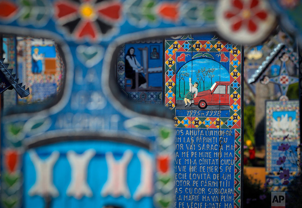 The story of a child who was run over by a car is depicted on her cross, center right, in the Merry Cemetery, in Sapanta, northwestern Romania, Monday, Sept. 11, 2017. (AP Photo/Vadim Ghirda)