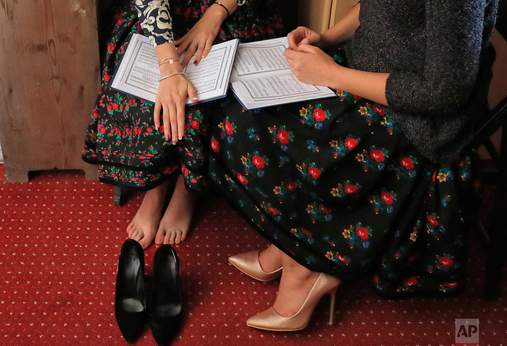 Women from the church quire take a break during a religious service at the church  in the Merry Cemetery, in Sapanta, northwestern Romania, Sunday, Sept. 10, 2017. (AP Photo/Vadim Ghirda)