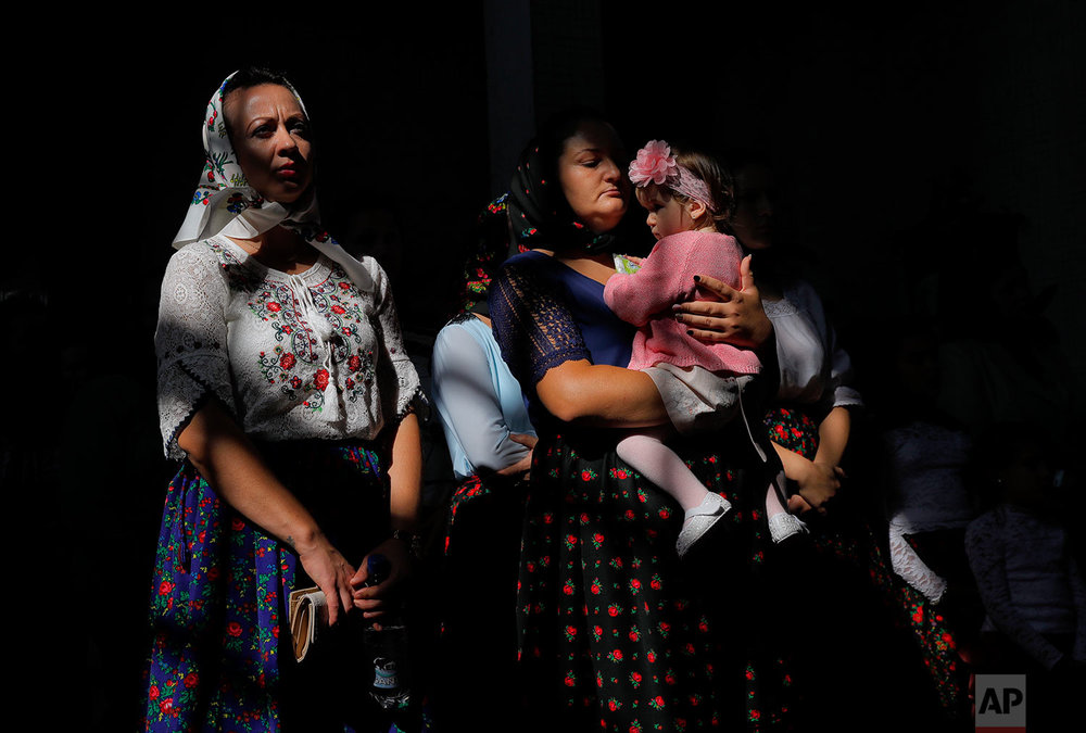 A woman holds a child during a religious service at the church in the Merry Cemetery, in Sapanta, northwestern Romania, Sunday, Sept. 10, 2017. (AP Photo/Vadim Ghirda)