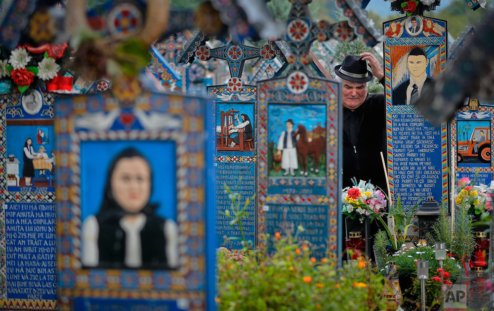 A man cries at a relative's grave standing between the painted crosses in the Merry Cemetery, in Sapanta, northwestern Romania, Sunday, Sept. 10, 2017. (AP Photo/Vadim Ghirda)