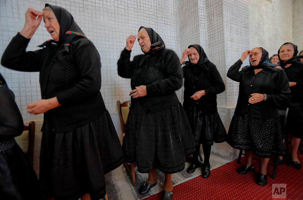 Women cross themselves during a religious service at the church in the Merry Cemetery, in Sapanta, northwestern Romania, Sunday, Sept. 10, 2017. (AP Photo/Vadim Ghirda)