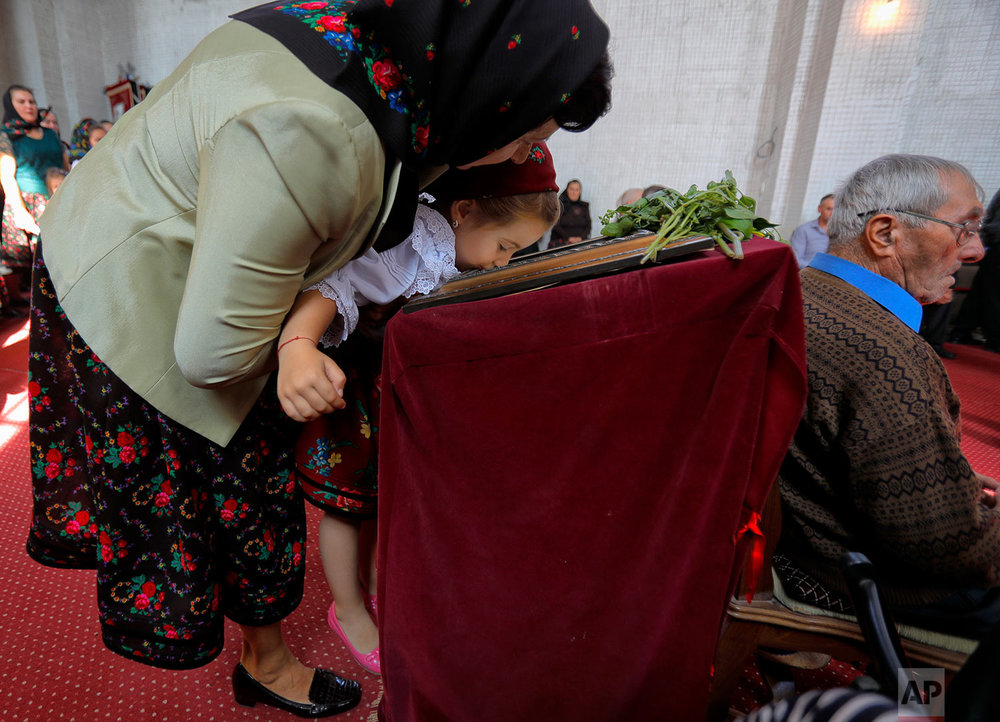 A woman lifts a little girl to kiss an icon during a religious service at the church in the Merry Cemetery, in Sapanta, northwestern Romania, Sunday, Sept. 10, 2017. (AP Photo/Vadim Ghirda)