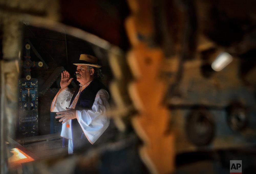Sculptor Dumitru Pop Tincu, 62, is reflected in a mirror at his workshop in Sapanta, northwestern Romania, Sunday, Sept. 10, 2017. (AP Photo/Vadim Ghirda)