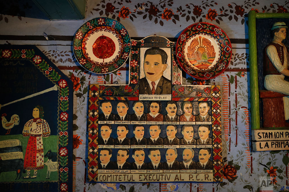A naive representation of former communist dictator Nicolae Ceausescu and the Communist party leadership by local wood sculptor Stan Ioan Patras, who in1935, started the Merry Cemetery, hangs on the wall of his memorial house, in Sapanta, northwestern Romania, Monday, Sept. 11, 2017. (AP Photo/Vadim Ghirda)