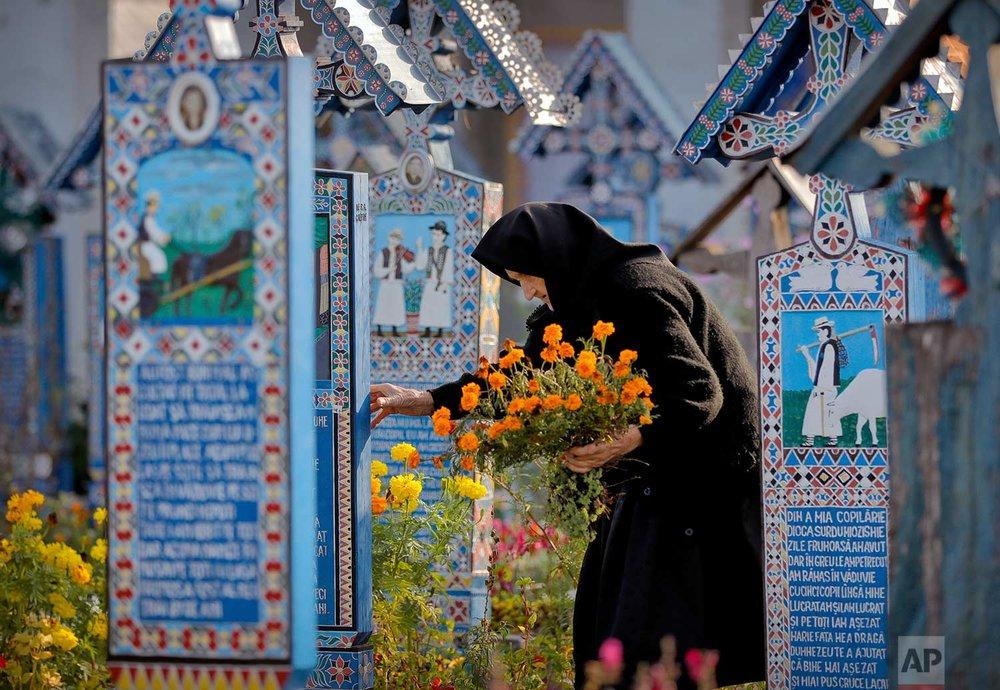 An elderly woman holds flowers, walking between painted crosses in the Merry Cemetery, in Sapanta, northwestern Romania, Sunday, Sept. 10, 2017. (AP Photo/Vadim Ghirda)