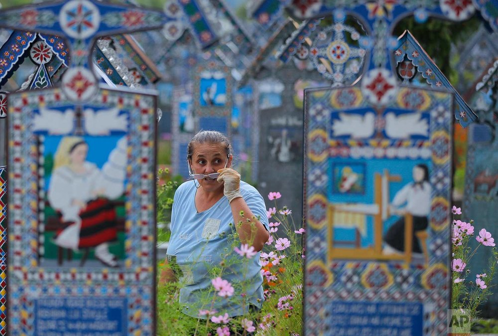A woman removes her glasses while cleaning a grave in the Merry Cemetery, in Sapanta, northwestern Romania, Saturday, Sept. 9, 2017. (AP Photo/Vadim Ghirda)