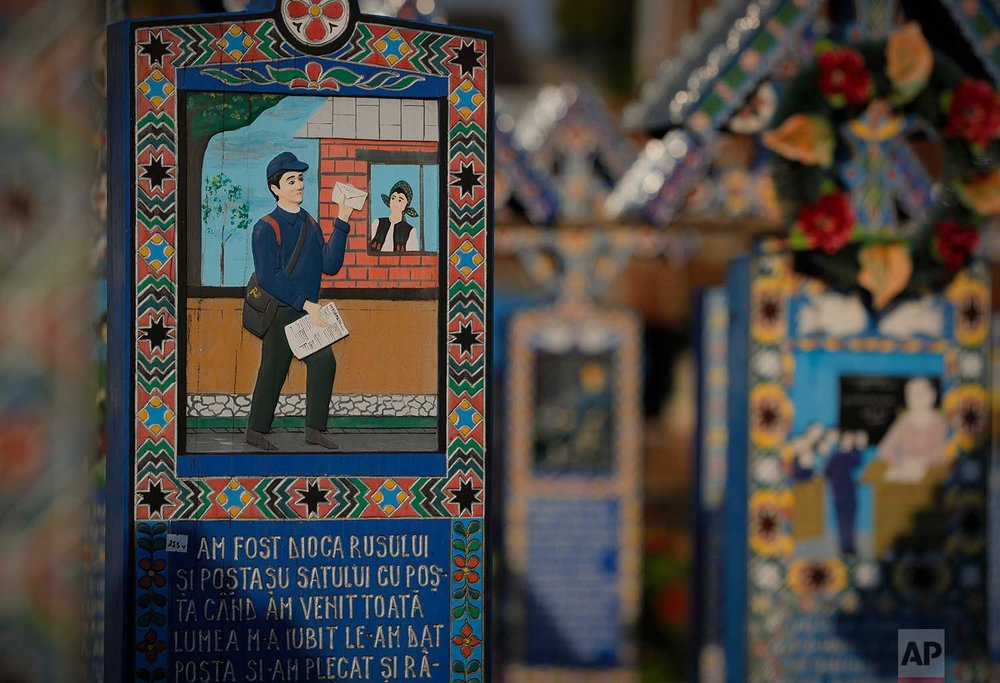 Crosses show depictions of the deceased and short stories of their lives and circumstances of their death in the Merry Cemetery, in Sapanta, northwestern Romania, Monday, Sept. 11, 2017. (AP Photo/Vadim Ghirda)