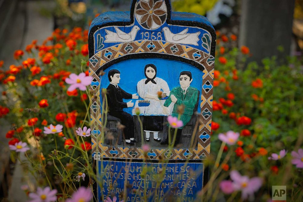 Crosses show depictions of the deceased and short stories of their lives and circumstances of their death in the Merry Cemetery, in Sapanta, northwestern Romania, Sunday, Sept. 10, 2017. (AP Photo/Vadim Ghirda)