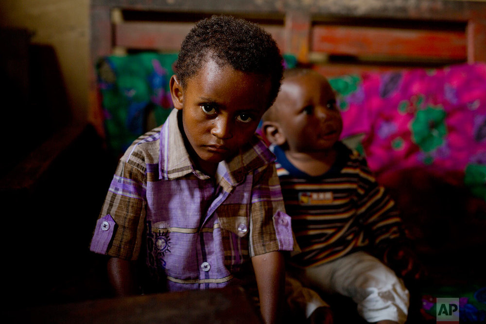 In this photo taken Aug. 10, 2016, 8-year-old Michael sits at his mother's house in the Congo Ituri province capital Bunia. Michael has never met his father, and only knows that he was a foreigner from one of the peacekeeping missions in the country.  (AP Photo/Jerome Delay)