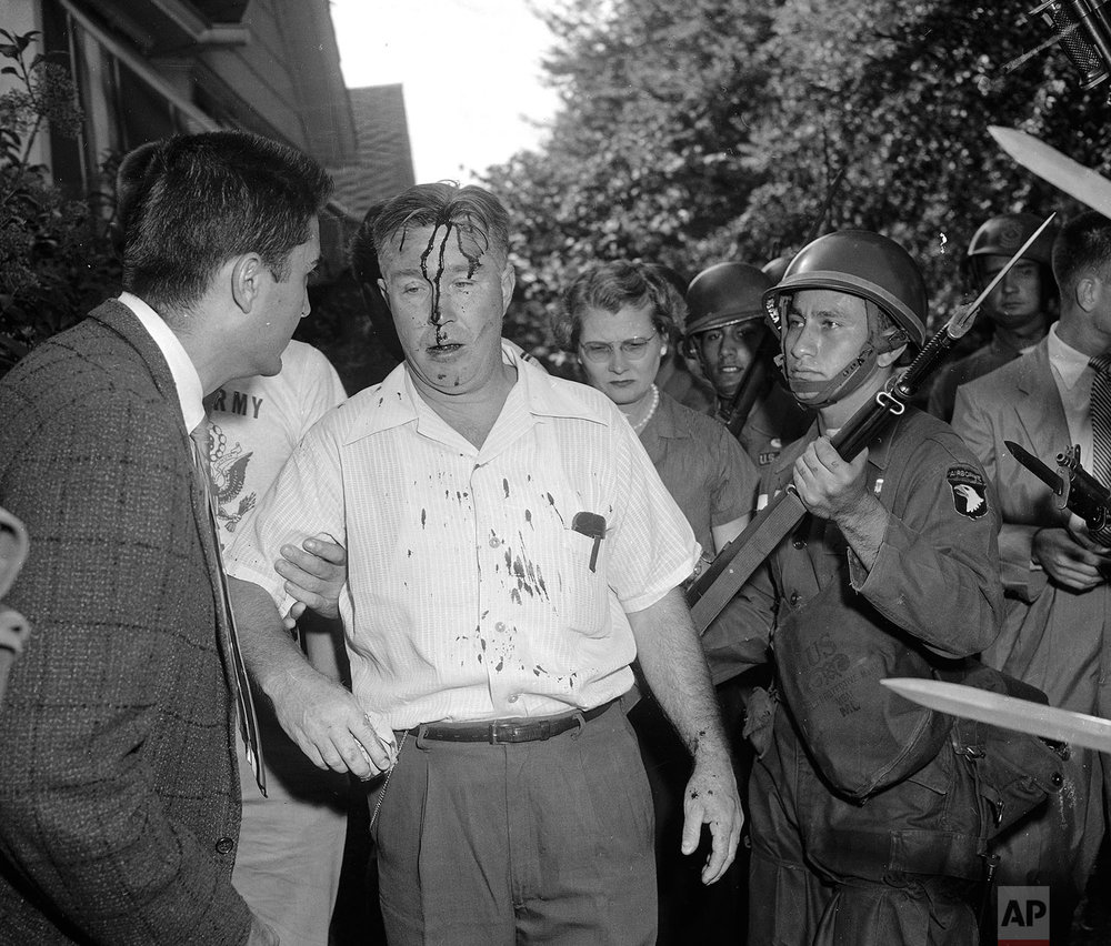 In this Sept. 25, 1957  photo, a U.S. Army paratrooper uses the butt of his rifle to nudge along a man identified as C.E. Blake, who was hit in the head when he tried to take a weapon from a trooper near Central High School in Little Rock, Ark., where integration is being enforced by the Army. (AP Photo)