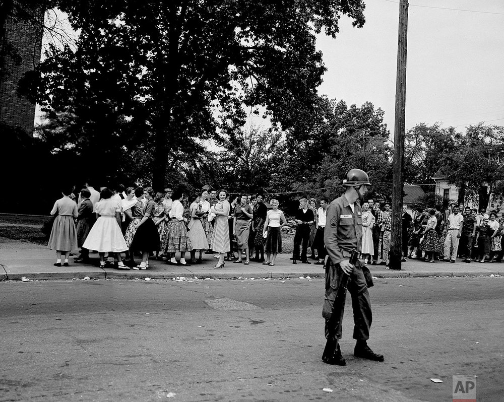 During a fire drill at Central High School in Little Rock, Ark., Minnie Brown, one of the nine black students escorted into school, stands with a group of white classmates outside the school, Sept. 25, 1957. (AP Photo)