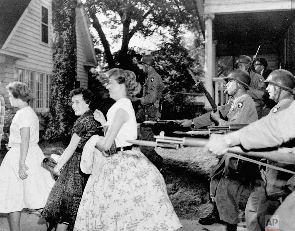 In this Sept. 25, 1957,  photo, white girls from Central High School laugh as troopers with bayonets force them to move in Little Rock, Ark.  (AP Photo)