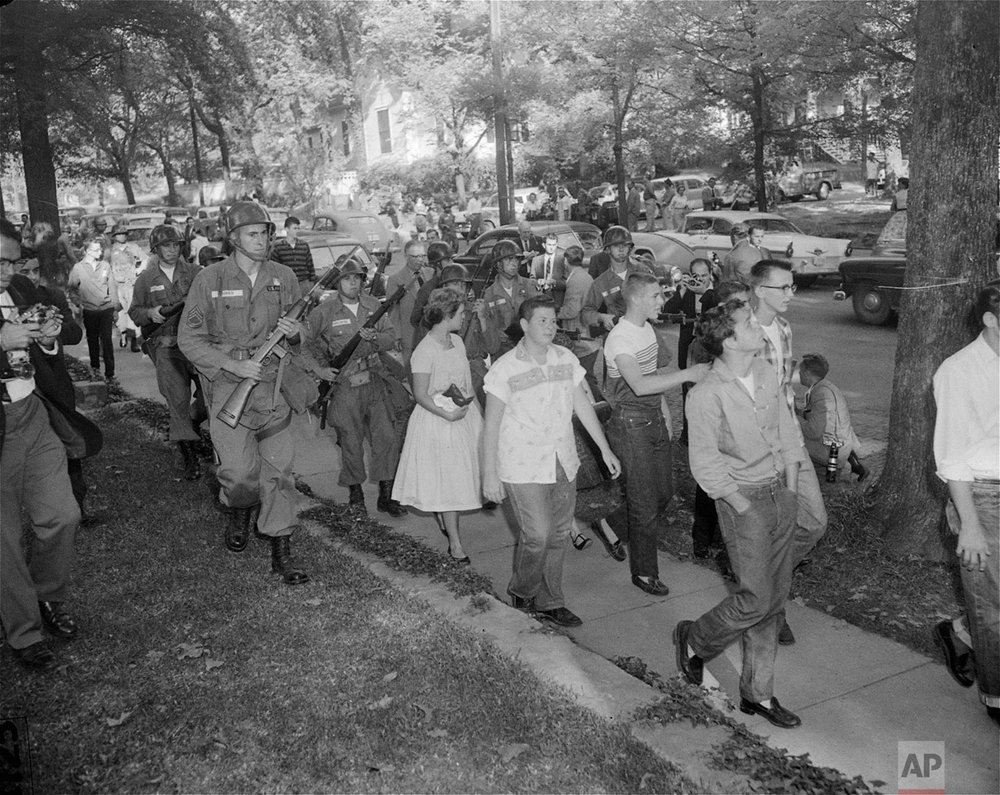 Troopers of the 101st Airborne Division keep a small crowd moving that had gathered September 25, 1957, across the street from Central High School, Little Rock, AR.  (AP Photo)
