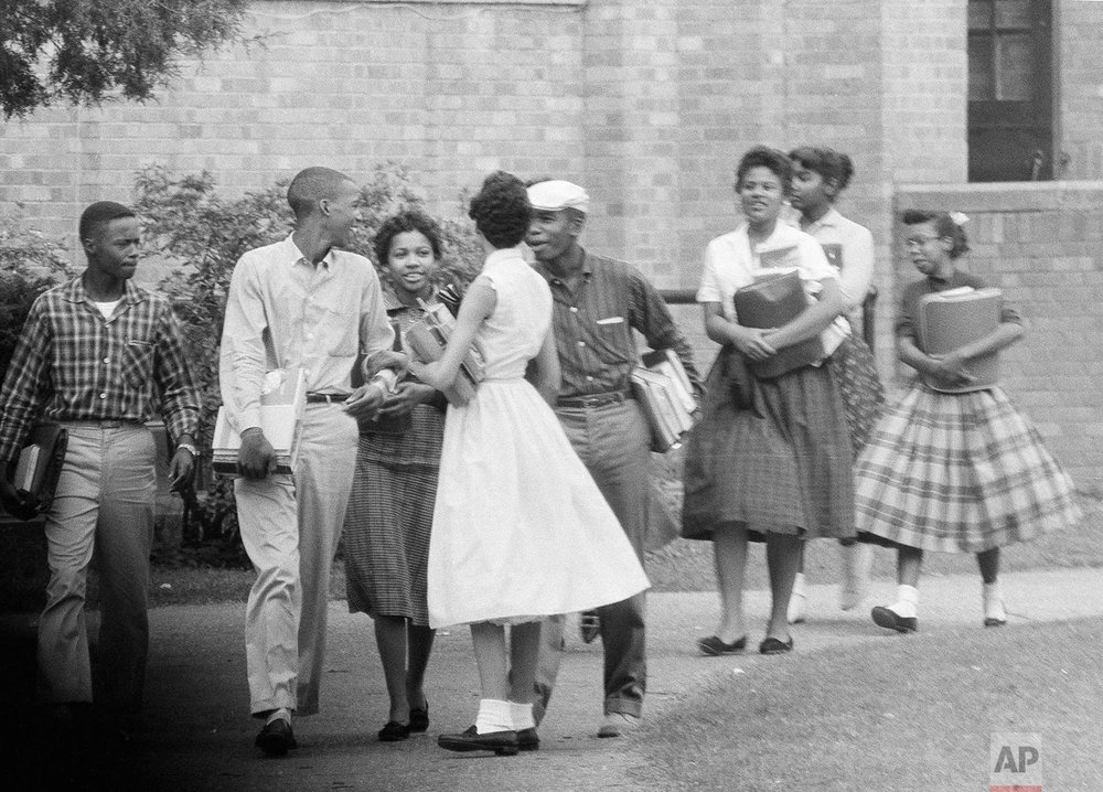 In this Oct. 2, 1957, photo, the first black students to enroll at Central High School in Little Rock, Ark., leave the building and walk toward a waiting Army station wagon following their classes. Monday, Sept. 25, 2017, marks the 60th anniversary of when nine black students enrolled at the Arkansas school. One of the nine students is obscured by another student in this photograph. (AP Photo/Ferd Kaufman)