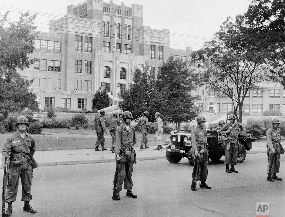 A command jeep patrols the area in front of Central High School in Little Rock, Ark., Sept. 25, 1957, as troops of the 101st Airborne Division stand with fixed bayonets.  The troops were sent to keep order in the integration of the school.  (AP Photo)