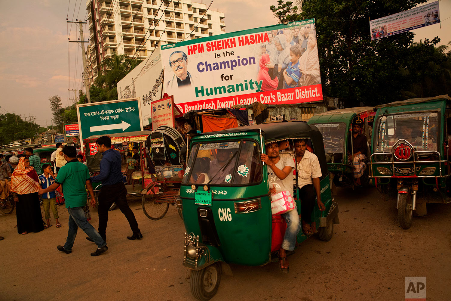 In this Saturday, Sept. 23, 2017 photo, Bangladeshis crowd a tuk-tuk on a street with a billboard in appreciation of Bangladesh's Prime Minister Sheikh Hasina for sheltering Rohingya Muslims fleeing Myanmar, in Cox's Bazar, Bangladesh. (AP Photo/Bernat Armangue)