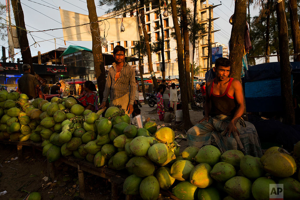 In this Friday, Sept. 22, 2017 photo, local coconut vendors wait for customers near Cox's Bazar beach in Bangladesh. (AP Photo/Bernat Armangue)