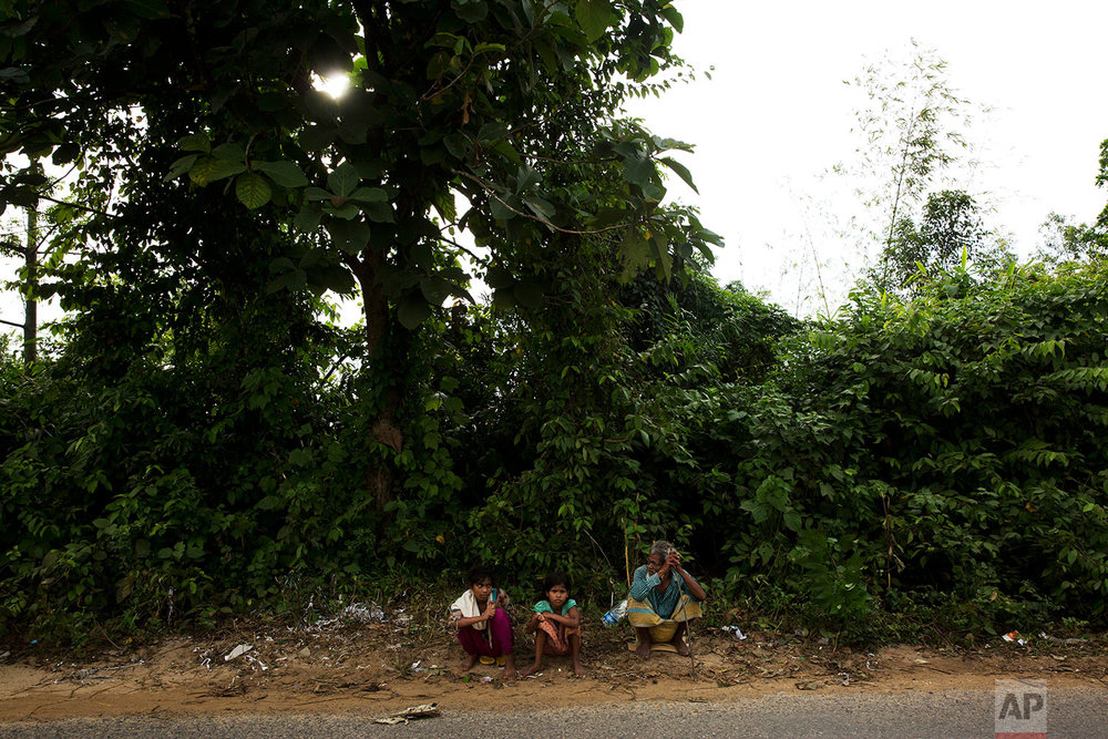 In this Saturday, Sept. 23, 2017 photo, newly arrived Rohingya Muslims beg on the road between Kutupalong and Cox Bazar, Bangladesh. (AP Photo/Bernat Armangue)